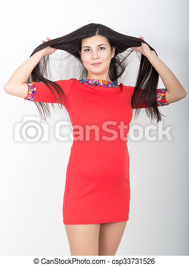 young pretty slim asian woman standing in a little red dress - csp33731526