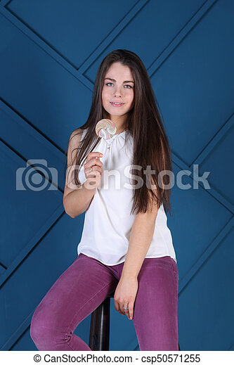 Young pretty woman poses on stool with lollipop in blue studio - csp50571255