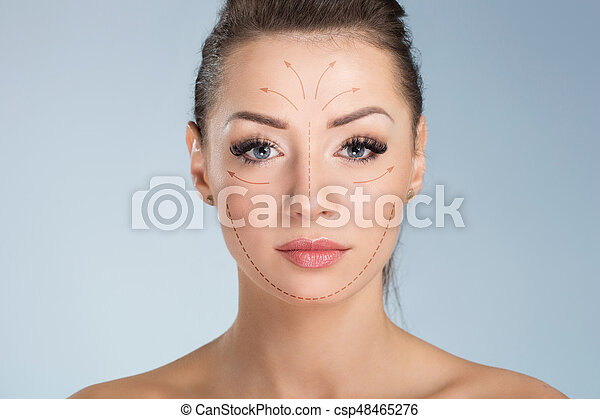 Young pretty woman with surgical markers on face