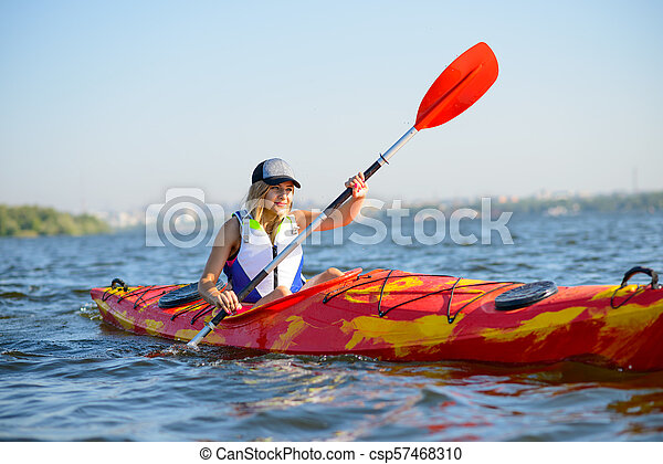 Young Professional Woman Kayaker Paddling Kayak on River under Bright Morning Sun. Sport and Active Lifestyle Concept - csp57468310