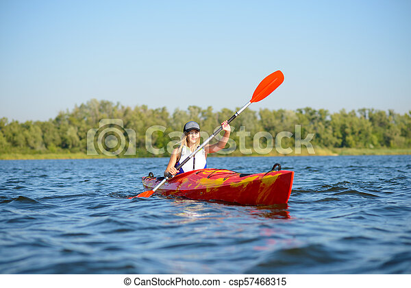 Young Professional Woman Kayaker Paddling Kayak on River under Bright Morning Sun. Sport and Active Lifestyle Concept - csp57468315