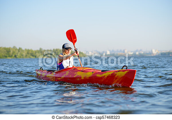 Young Professional Woman Kayaker Paddling Kayak on River under Bright Morning Sun. Sport and Active Lifestyle Concept - csp57468323