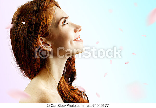 Young redhead woman over fresh blue background with swirl petals. - csp74949177