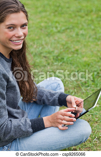 Young relaxed adult sitting down with her tablet computer while looking at the camera - csp9265066