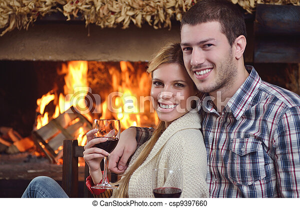Young romantic couple sitting and relaxing in front of fireplace at home - csp9397660