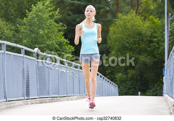 Young running woman trains her stamina outdoor - csp32740832