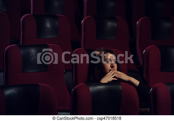 Young scared girl watching movie in cinema theater - csp47018518