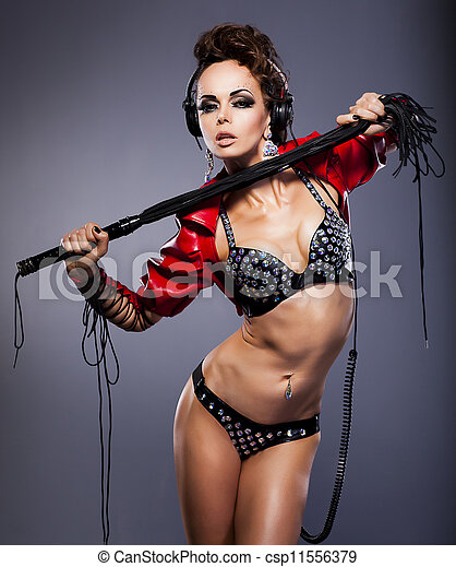 Young sexy woman mistress in headphones and whip in erotic pose - csp11556379