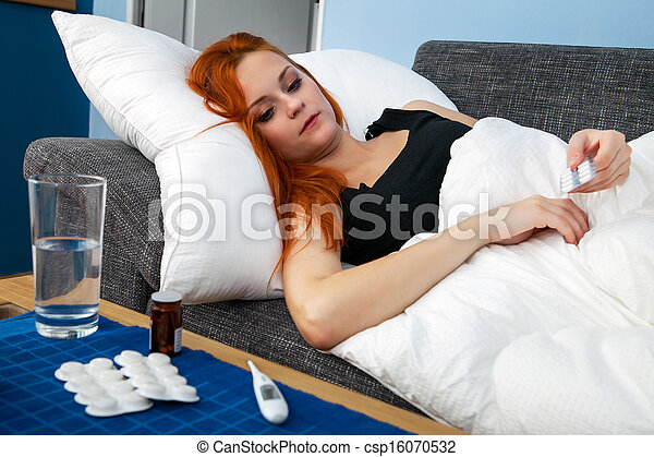 Young sick woman holding pills - csp16070532