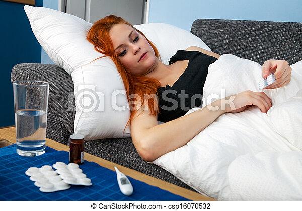 Young sick woman holding pills - csp16070532