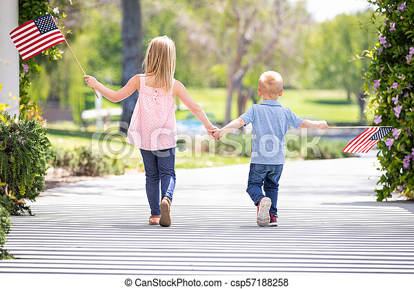 Young Sister and Brother Holding Hands and Waving American Flags At The Park - csp57188258