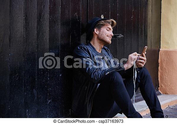 Young smartphone man sitting street - csp37163973