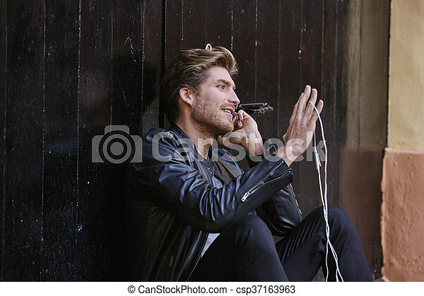 Young smartphone man sitting street - csp37163963