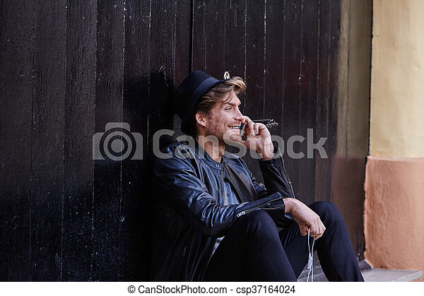 Young smartphone man sitting street - csp37164024