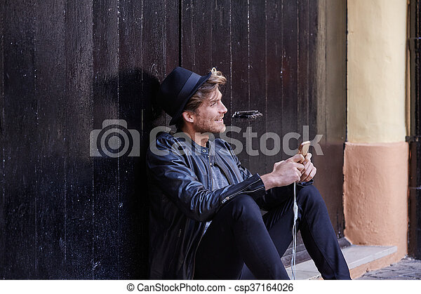 Young smartphone man sitting street - csp37164026