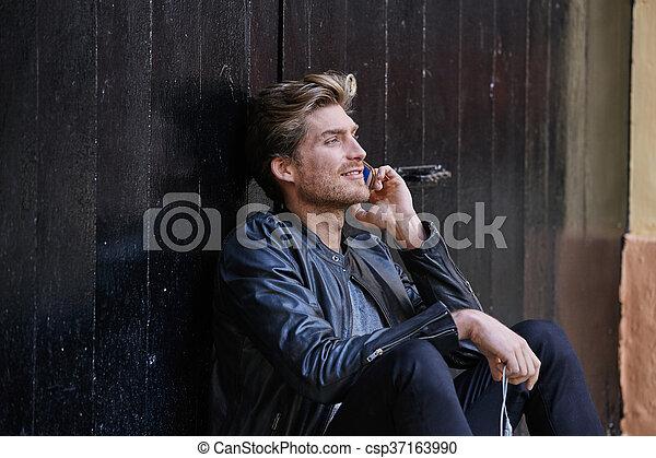 Young smartphone man sitting street - csp37163990