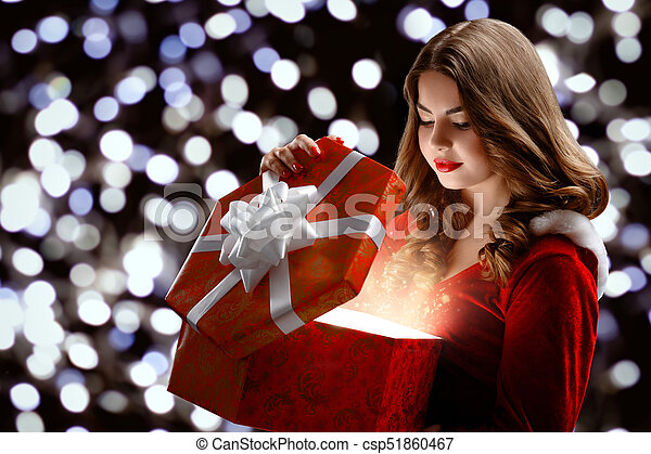 Young smiley girl in a snow maiden s suit opens a gift for new year ...