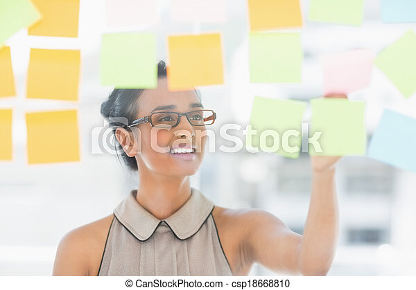 Young smiling designer looking at sticky notes on window - csp18668810