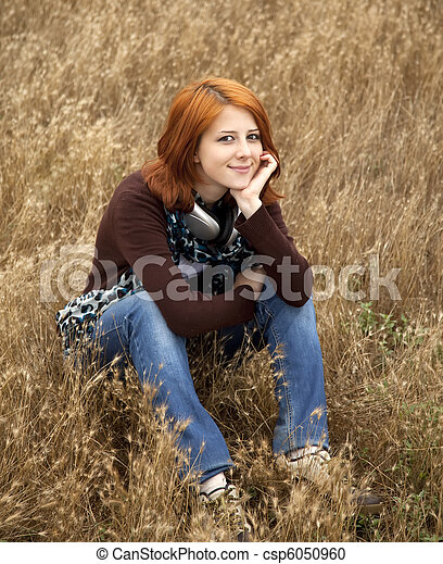 Young smiling girl with headphones at field. - csp6050960