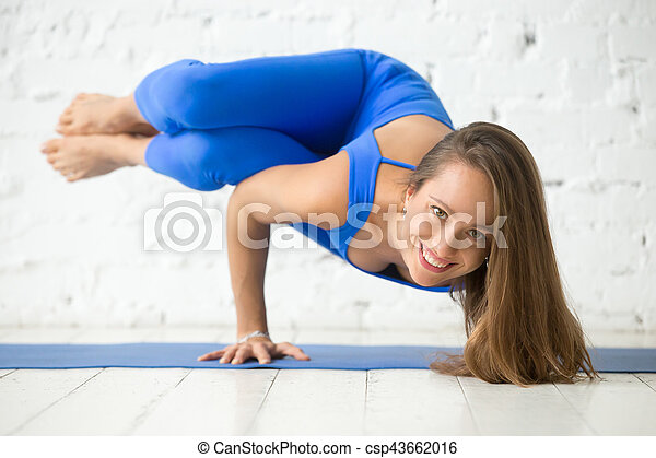 young smiling woman in parsva bakasana pose white studio