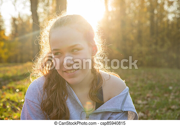 Young smiling woman in white hoodie sitting in the autumn park - csp85940815