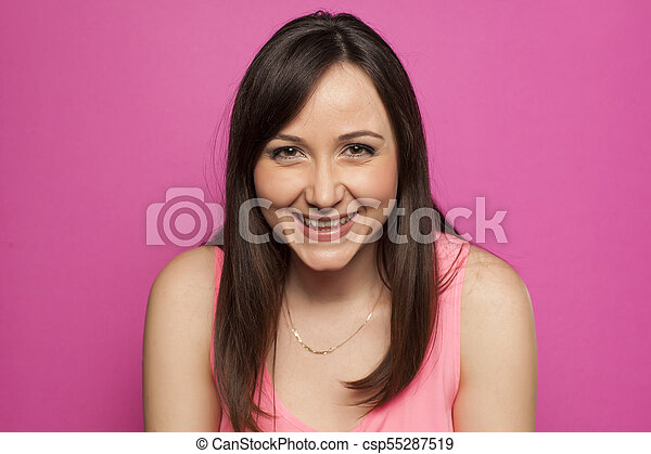 Young smiling woman on pink background - csp55287519