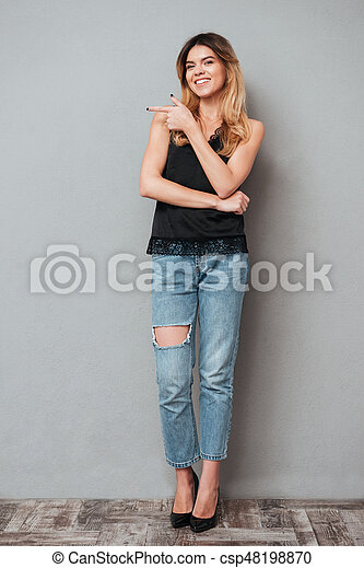 Young smiling woman pointing at copy space - csp48198870