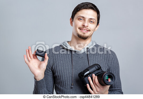 young smilling photographer in shirt  holds the battery for DSLR - csp44841289