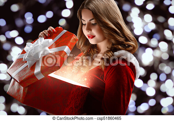 Young snow maiden in the red suit opens a gift for new year 2018 ...
