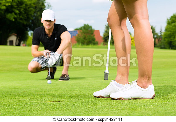 Young sportive couple playing golf on a course - csp31427111