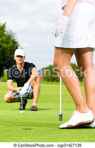 Young sportive couple playing golf on a course - csp31427139
