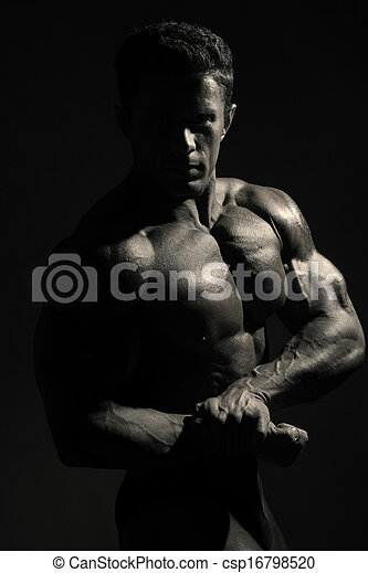 Young sports male with a naked torso against a dark background. Monochrome photos athlete - csp16798520