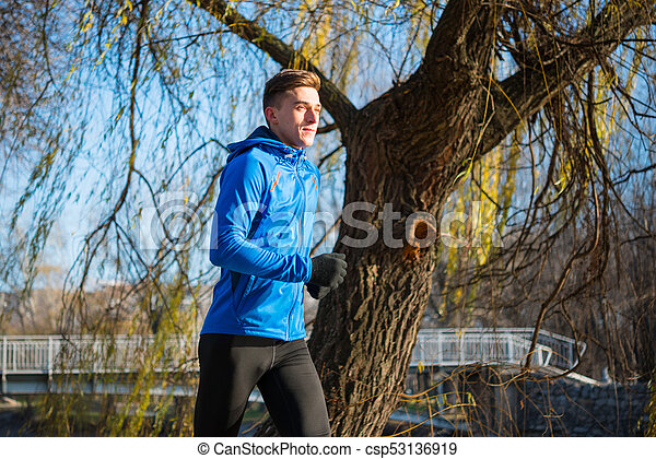 Young Sports Man Running in the Park in Cold Sunny Autumn Morning. Healthy Lifestyle and Sport Concept. - csp53136919