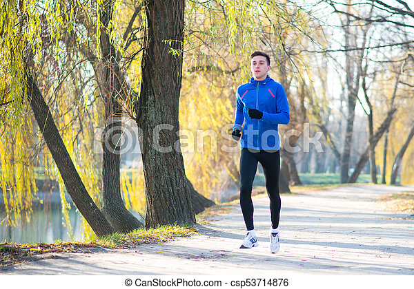 Young Sports Man Running in the Park in Cold Sunny Autumn Morning. Healthy Lifestyle and Sport Concept. - csp53714876