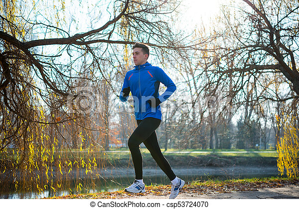 Young Sports Man Running in the Park in Cold Sunny Autumn Morning. Healthy Lifestyle and Sport Concept. - csp53724070