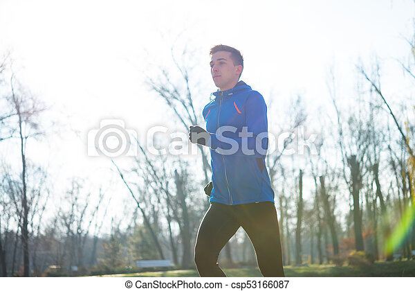 Young Sports Man Running in the Park in Cold Sunny Autumn Morning. Healthy Lifestyle and Sport Concept. - csp53166087