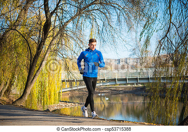Young Sports Man Running in the Park in Cold Sunny Autumn Morning. Healthy Lifestyle and Sport Concept. - csp53715388