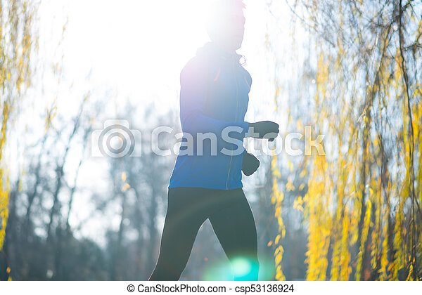 Young Sports Man Running in the Park in Cold Sunny Autumn Morning. Healthy Lifestyle and Sport Concept. - csp53136924