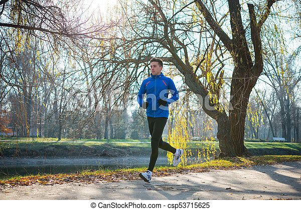Young Sports Man Running in the Park in Cold Sunny Autumn Morning. Healthy Lifestyle and Sport Concept. - csp53715625