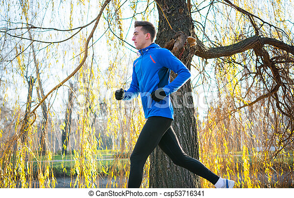 Young Sports Man Running in the Park in Cold Sunny Autumn Morning. Healthy Lifestyle and Sport Concept. - csp53716341