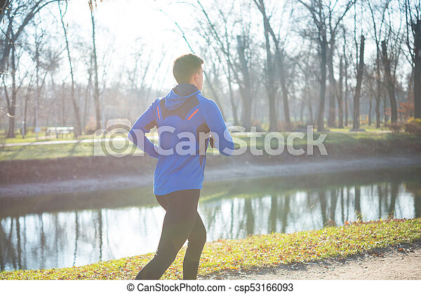 Young Sports Man Running in the Park in Cold Sunny Autumn Morning. Healthy Lifestyle and Sport Concept. - csp53166093