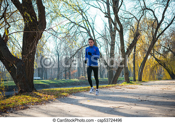 Young Sports Man Running in the Park in Cold Sunny Autumn Morning. Healthy Lifestyle and Sport Concept. - csp53724496