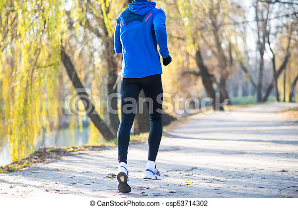 Young Sports Man Running in the Park in Cold Sunny Autumn Morning. Healthy Lifestyle and Sport Concept. - csp53714302