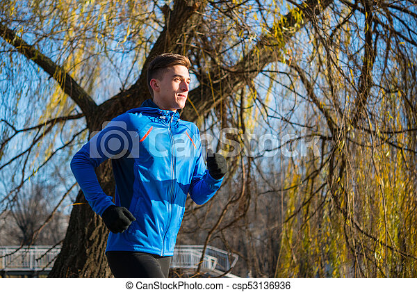 Young Sports Man Running in the Park in Cold Sunny Autumn Morning. Healthy Lifestyle and Sport Concept. - csp53136936