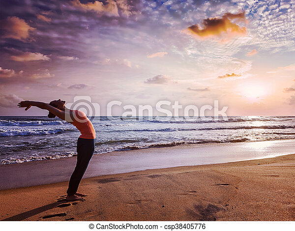 young sporty fit woman doing yoga sun salutation surya
