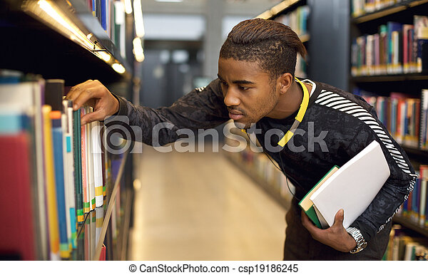 Young student looking for reference books at university library - csp19186245