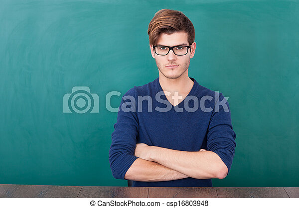 Young Student Standing In Front Of Chalkboard - csp16803948