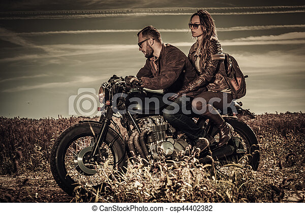 Young, stylish cafe racer couple on vintage custom motorcycles in field - csp44402382