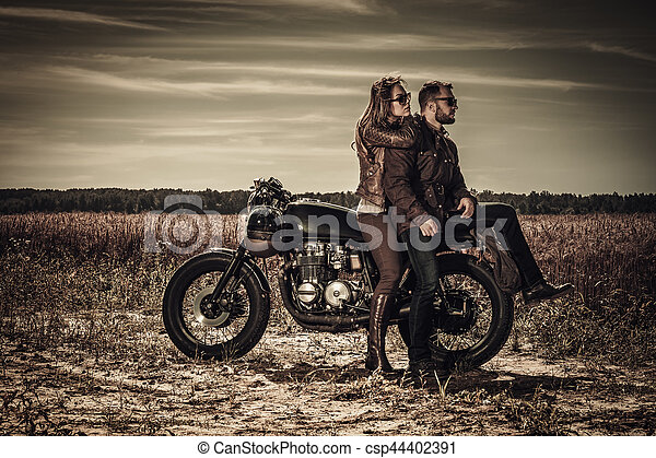 Young, stylish cafe racer couple on vintage custom motorcycles in field - csp44402391