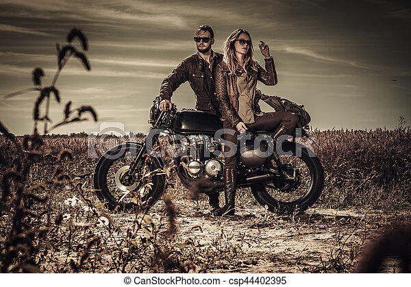 Young, stylish cafe racer couple on vintage custom motorcycles in field - csp44402395